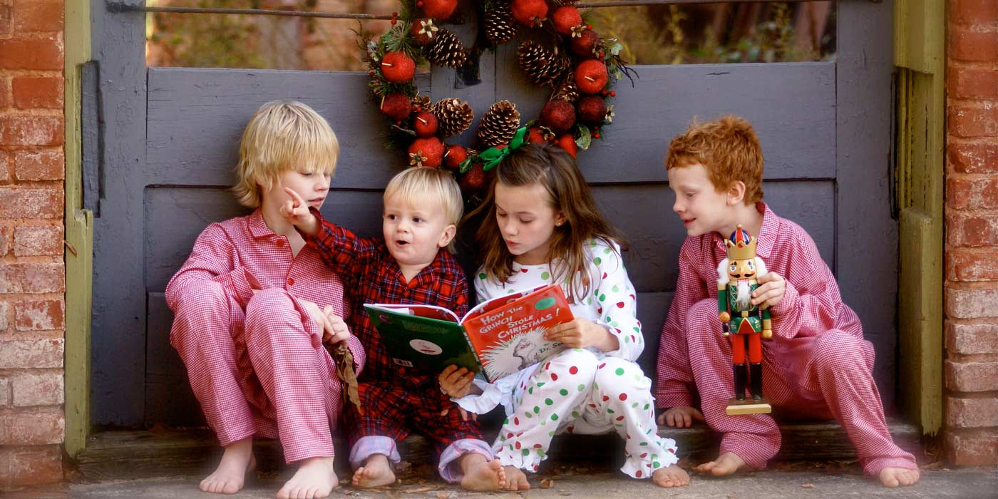Four children reading a Christmas book